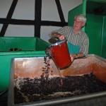 Die Maische wird in Bottiche geschöpft